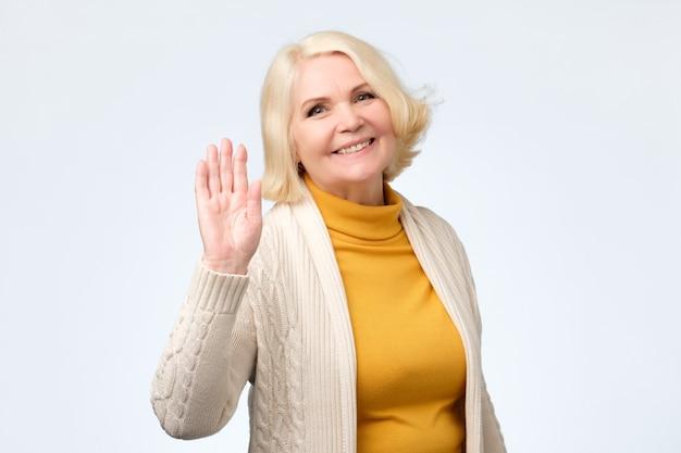 Mulher idosa acenando com a mão e cumprimentando a amiga