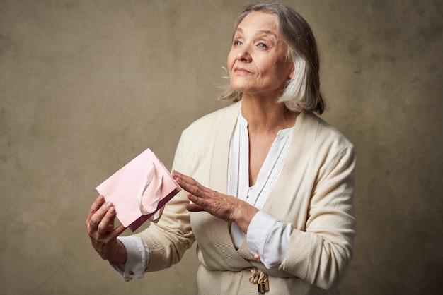 Mulher idosa alegre com uma sacola de presente no estúdio de férias