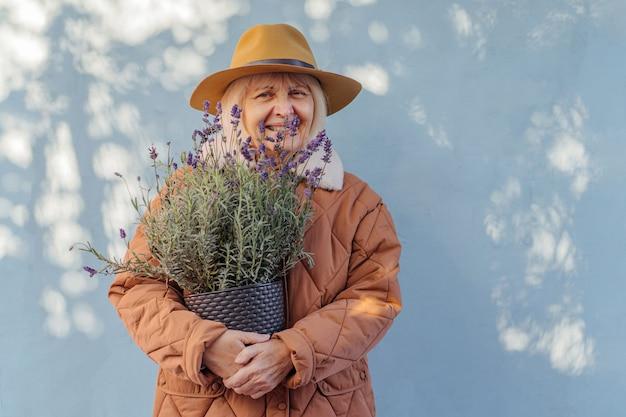 Mulher idosa alegre em agasalhos elegantes, sorrindo enquanto carrega um vaso com flores frescas