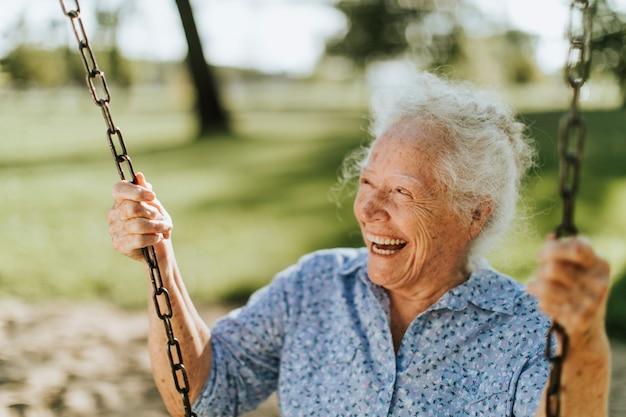 Mulher idosa alegre em um balanço em um parquinho