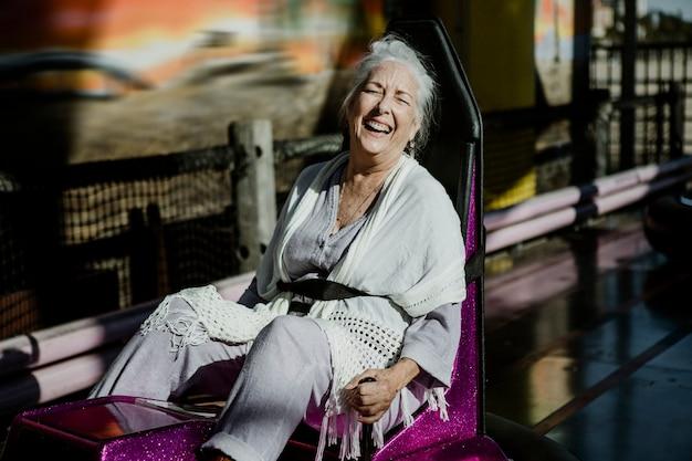 Mulher idosa alegre em um carro de choque em um parque de diversões