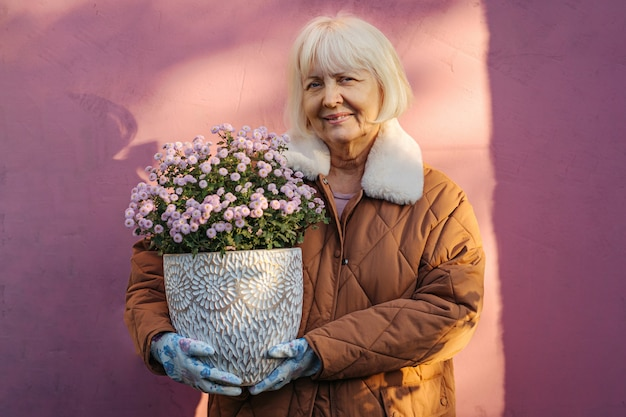 Mulher idosa alegre fazendo um hobby e gosta de jardinagem.