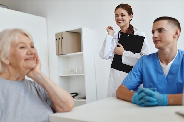 Mulher idosa alegre na recepção do hospital se comunica com a enfermeira e o médico