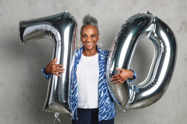 Mulher idosa alegre segurando balões prateados para comemorar seu 70º aniversário