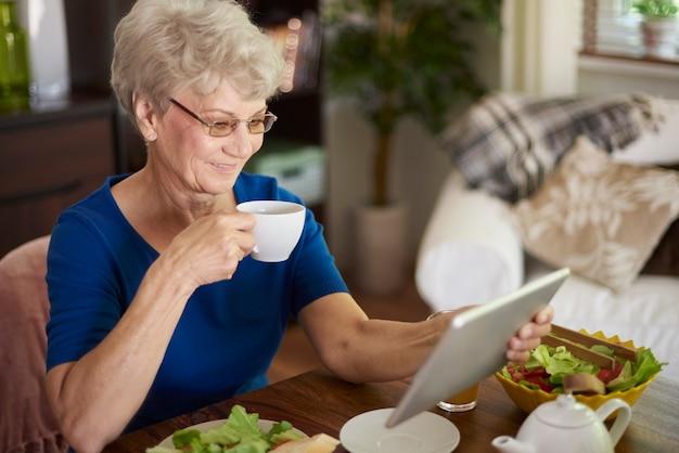 Mulher idosa alegre tomando café da manhã e navegando na internet