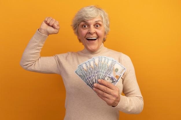 Mulher idosa alegre usando um suéter cremoso de gola alta e segurando dinheiro para levantar o dinheiro