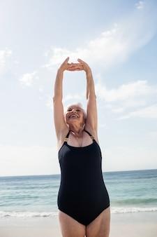 Mulher idosa alongando-se na praia