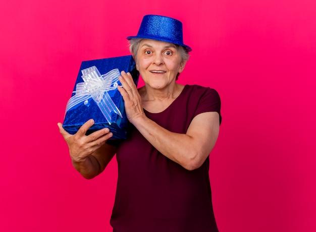 Mulher idosa animada com chapéu de festa segurando uma caixa de presente isolada na parede rosa