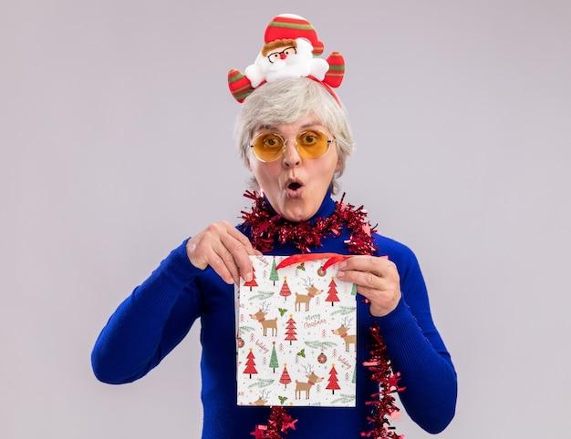 Mulher idosa animada usando óculos de sol com faixa de papai noel e guirlanda no pescoço segurando uma sacola de papel para presente