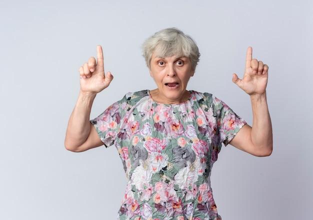 Mulher idosa ansiosa aponta para cima com as duas mãos isoladas na parede branca