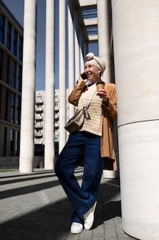 Mulher idosa ao ar livre na cidade falando ao telefone enquanto toma café