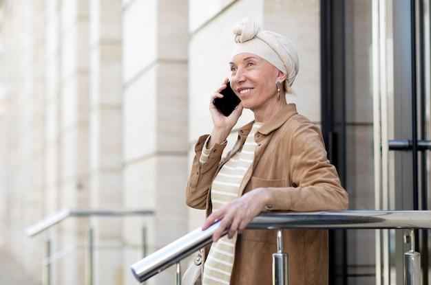 Mulher idosa ao ar livre na cidade falando ao telefone