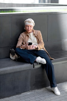 Mulher idosa ao ar livre na cidade, sentada no banco e usando o smartphone