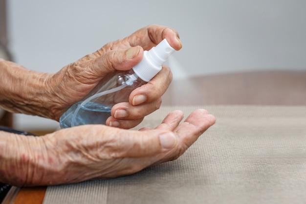 Mulher idosa, aplicando álcool, limpando as mãos para ajudar a proteger do coronavírus covid-19