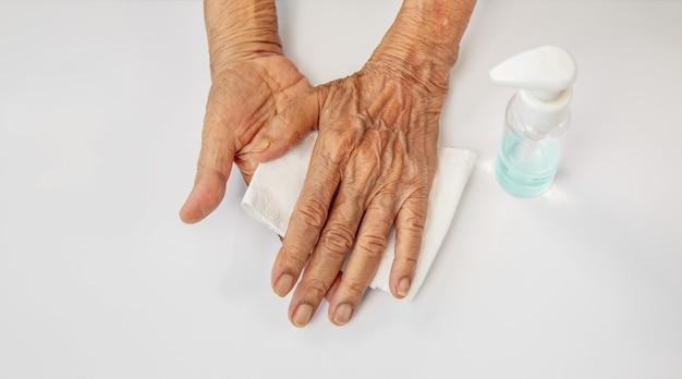 Mulher idosa aplicando gel de álcool, limpando as mãos para ajudar a proteger do coronavírus covid-19