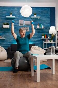 Mulher idosa aposentada levantando as mãos fazendo exercícios para os braços usando halteres sentada fitball, treinando resistência corporal