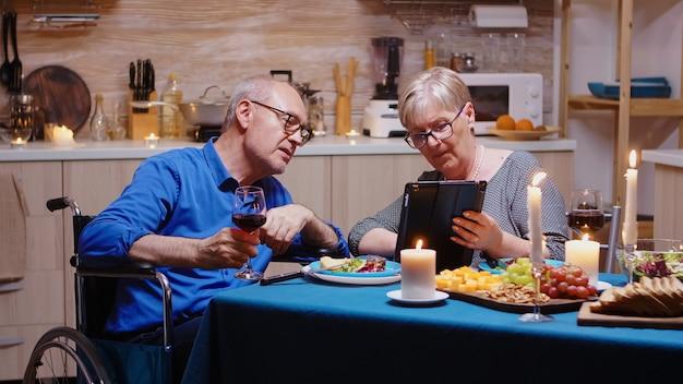 Mulher idosa aposentada mostrando tablet para homem paralisado, rolando e mostrando fotos. marido sênior deficiente imobilizado navegando no telefone, apreciando o homem festivo, bebendo uma taça de vinho tinto.