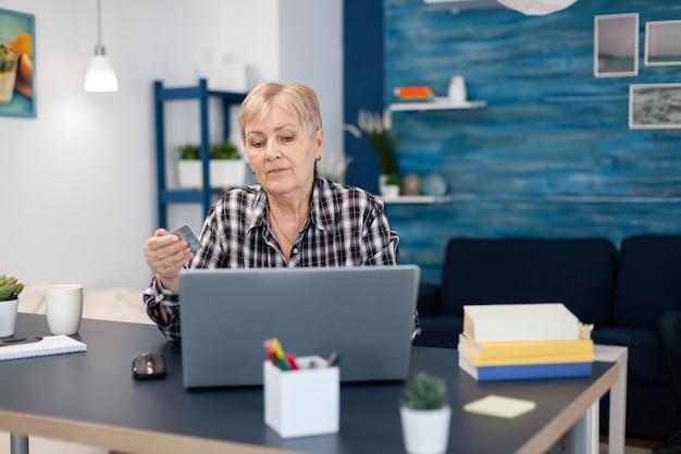 Mulher idosa aprendendo a fazer operações bancárias com cartão de crédito