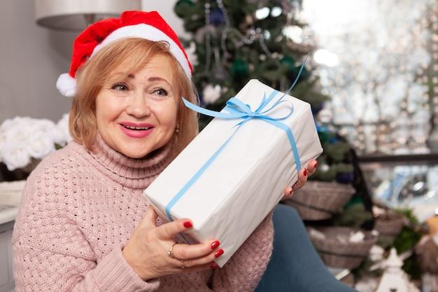 Mulher idosa, aproveitando a véspera de natal em casa
