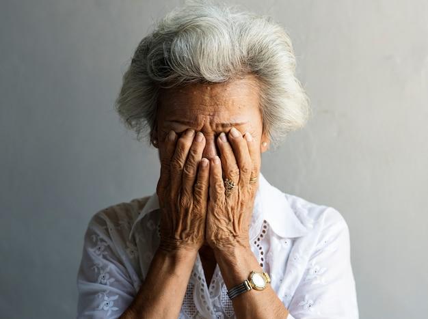 Mulher idosa asiática com as mãos cobertas de rosto