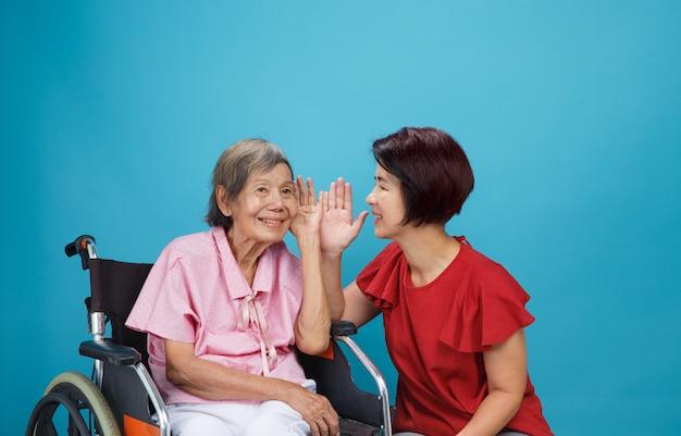 Mulher idosa asiática com perda de audição, com deficiência auditiva tenta falar com a filha