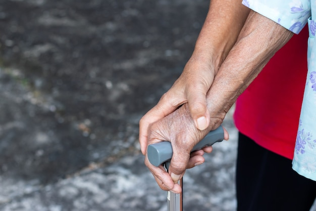 Mulher idosa asiática em pé com a mão em uma bengala com a mão da filha