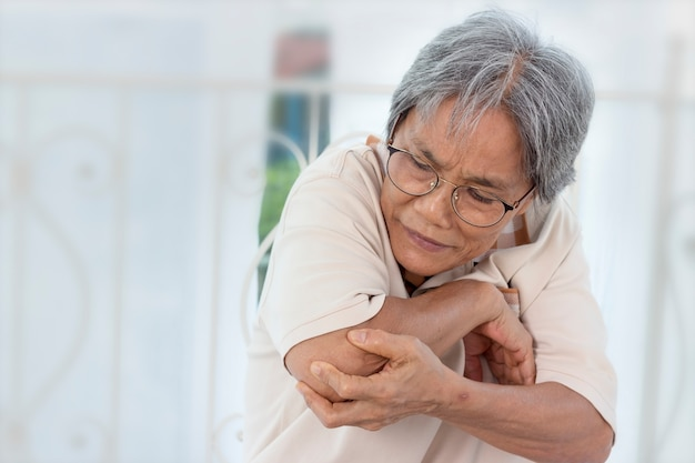 Mulher idosa asiática está tendo dores musculares.