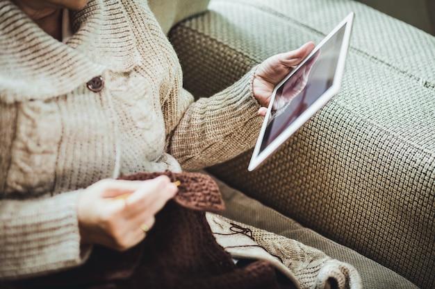 Mulher idosa asiática feliz tricotando cachecol marrom de crochê e tablet no sofá da sala de estar em casa