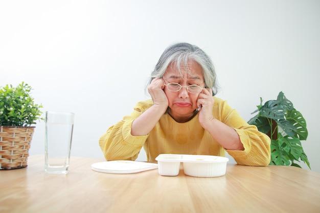 Mulher idosa asiática fica em casa durante a epidemia de coronavírus ela está cansada de comida embalada. conceito de prevenção da infecção pelo vírus covid-19