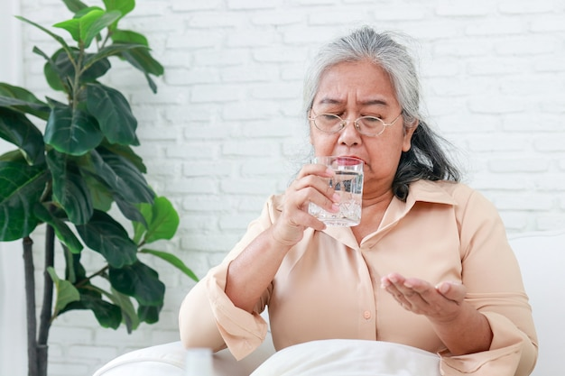 Mulher idosa asiática fica em casa ela está com gripe. ela está tomando analgésicos e bebendo água pura. o conceito de doença do idoso. cuidando de idosos durante o covid-19
