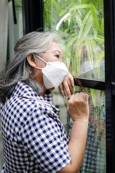 Mulher idosa asiática fique em casa para prevenir infecções. durante a epidemia de coronavírus, ela olhou pela janela, estressada com a possibilidade de viver a vida. conceito de isolamento doméstico, distanciamento social