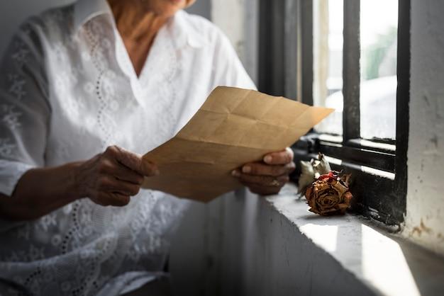 Mulher idosa asiática lendo uma carta antiga