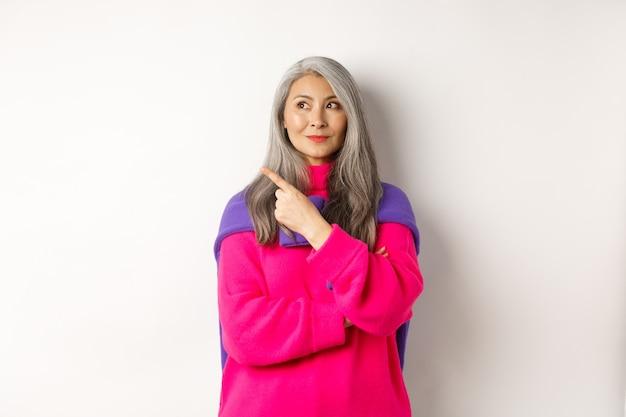 Mulher idosa asiática moderna e elegante apontando para o canto superior esquerdo, olhando para o logotipo com um sorriso satisfeito, usando um suéter rosa sobre fundo branco