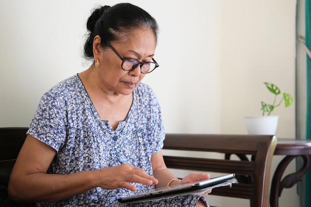 Mulher idosa asiática mostrando expressão facial séria ao usar seu gadget de tablet móvel