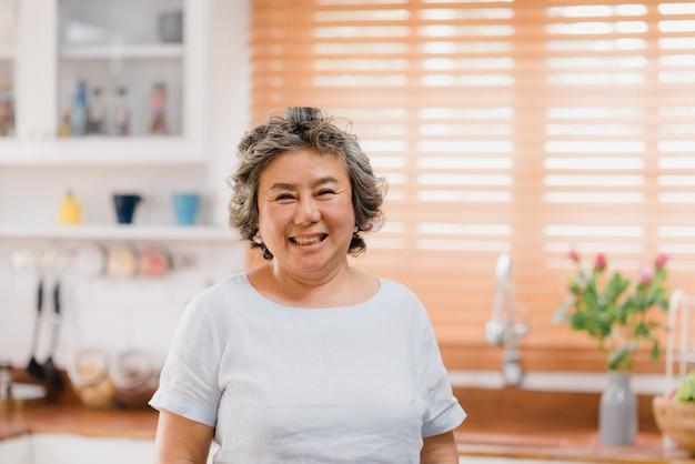 Mulher idosa asiática que sente feliz sorrindo e olhando à câmera quando relaxe na cozinha em casa.