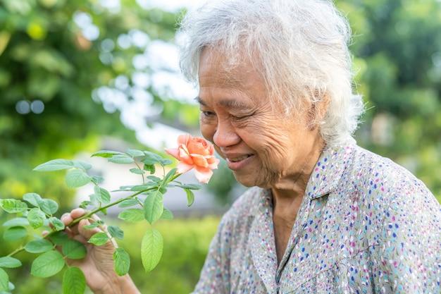 Mulher idosa asiática sênior ou idosa com flor rosa laranja rosada no jardim ensolarado.