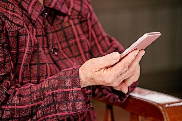 Mulher idosa asiática sentada e olhando algo em um smartphone moderno, fazendo conexão com outras pessoas em casa, tecnologia viva, close-up