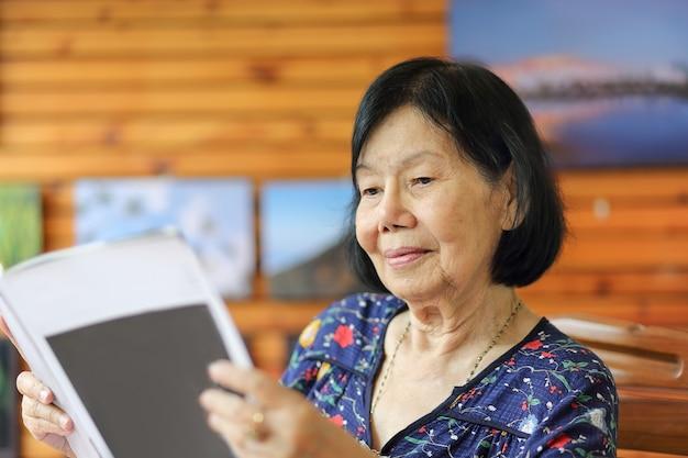 Mulher idosa asiática sorrindo enquanto lê uma revista