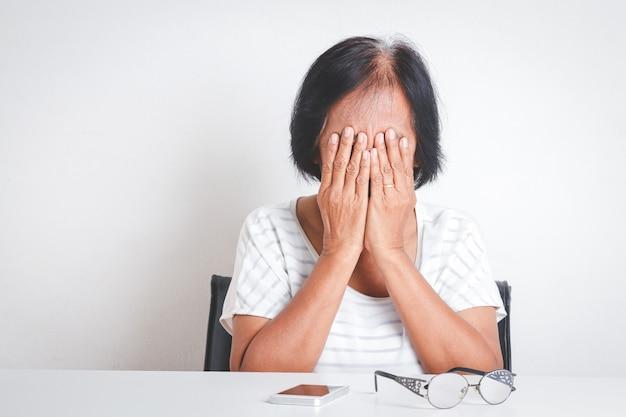 Mulher idosa asiática tem estresse sentindo-se muito preocupado com problemas com a vida de aposentadoria.