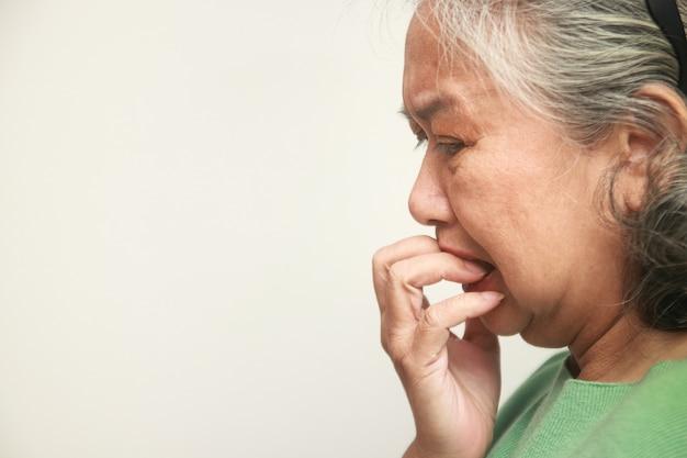 Mulher idosa asiática trancada em casa durante a epidemia de coronavírus ela estava estressada e preocupada. conceito de prevenção da infecção pelo vírus covid-19. copie o espaço