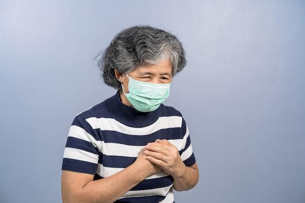 Mulher idosa asiática usando máscara cirúrgica no rosto e sentindo dor ao tocar no peito com coração