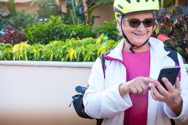 Mulher idosa ativa com bicicleta e capacete para e escreve uma mensagem em seu telefone inteligente