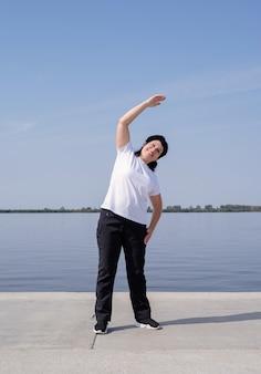 Mulher idosa ativa e feliz se exercitando perto da margem do rio