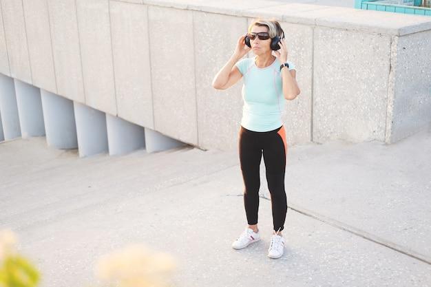 Mulher idosa ativa gosta de ouvir música após o treino de fitness na cidade com fones de ouvido e óculos de sol. mulher de aptidão desportiva. estilo de vida saudável. foto de alta qualidade