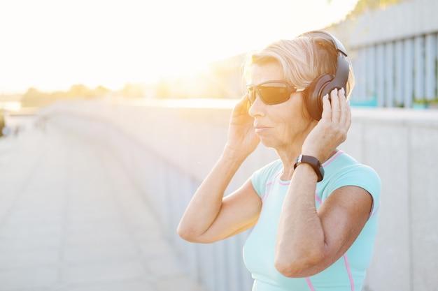 Mulher idosa ativa gosta de ouvir música após o treino de fitness na cidade com fones de ouvido e óculos de sol. relógio inteligente. mulher de aptidão desportiva. estilo de vida saudável. foto de alta qualidade