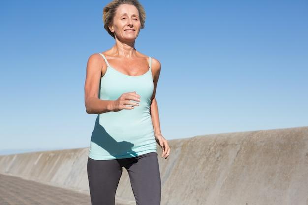 Mulher idosa ativa jogging no cais
