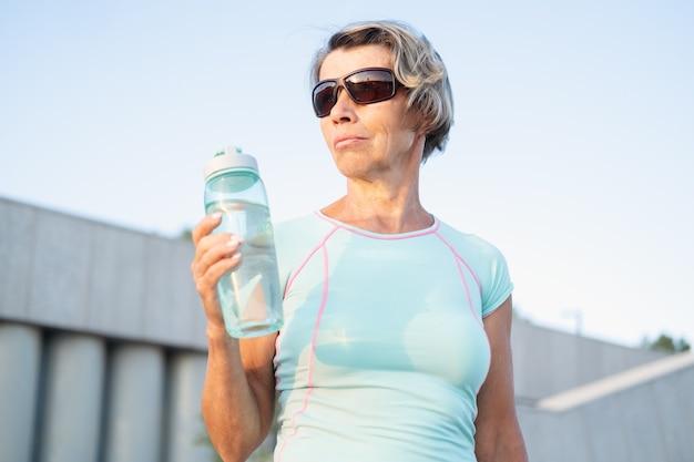 Mulher idosa ativa no treino de fitness na cidade bebe água, com óculos de sol. mulher de aptidão desportiva. estilo de vida saudável. foto de alta qualidade