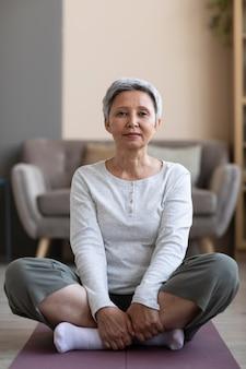 Mulher idosa ativa treinando em casa