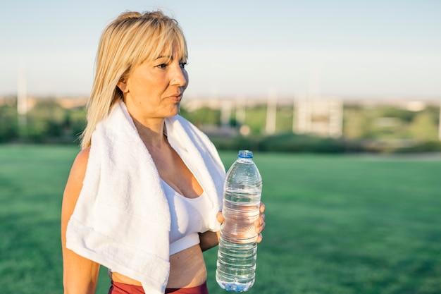 Mulher idosa atraente e pessoa idosa está correndo feliz e treina segurando uma garrafa de água e bebendo no parque na cidade ao ar livre, ela usa uma toalha no pescoço e veste roupas esportivas