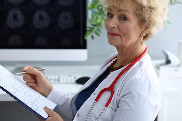 Mulher idosa atraente no médico do escritório